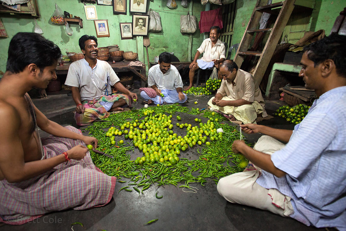 Workers string limes and peppers, which are used as a sort of good luck charm, at a shop in Kalighat, Kolata, India