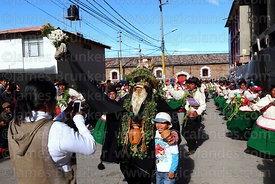 Woman taking photo of her son with man dressed as Dios del Lago / God of the Lake, Virgen de la Candelaria festival, Puno, Peru