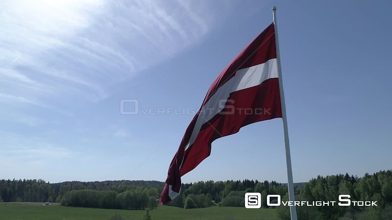 Aerial drone tilt and reveal shot of a large flag of Latvia on green countryside backdrop