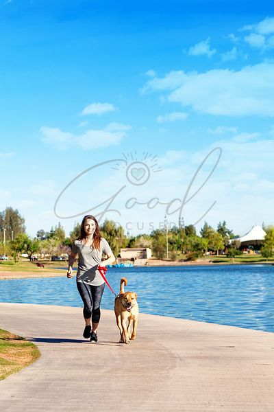 Woman Running in Park With Dog