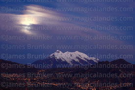 Full moon behind clouds, lights in suburbs of Zona Sur and Mt Illimani, La Paz, Bolivia