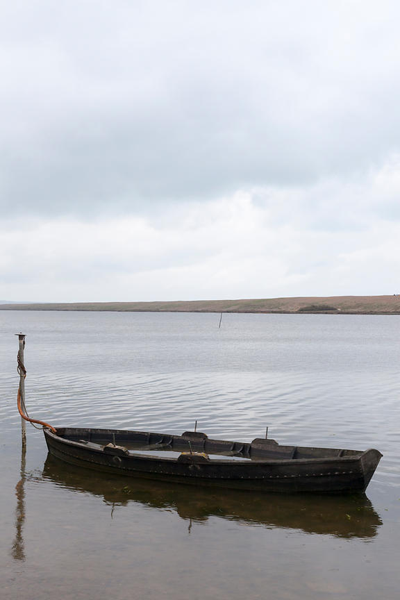 A waterlogged boat moored by a beach