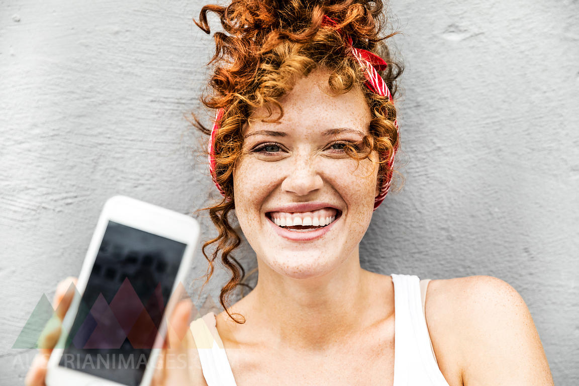 Happy redheaded woman showing cell phone