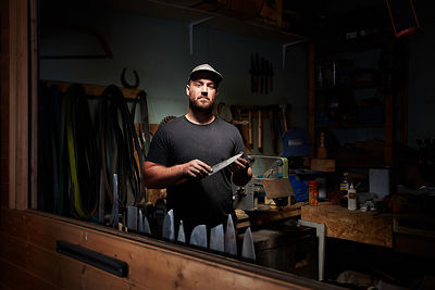 Environmental portrait of an artisan who hand makes knives in his riverside studio, by Douglas Kurn.