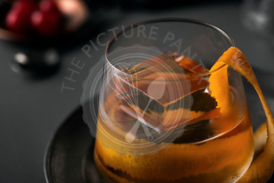 Old fashioned cocktail with large orange peel and artisan ice cube on a dark metal platter with cherry garnish.
