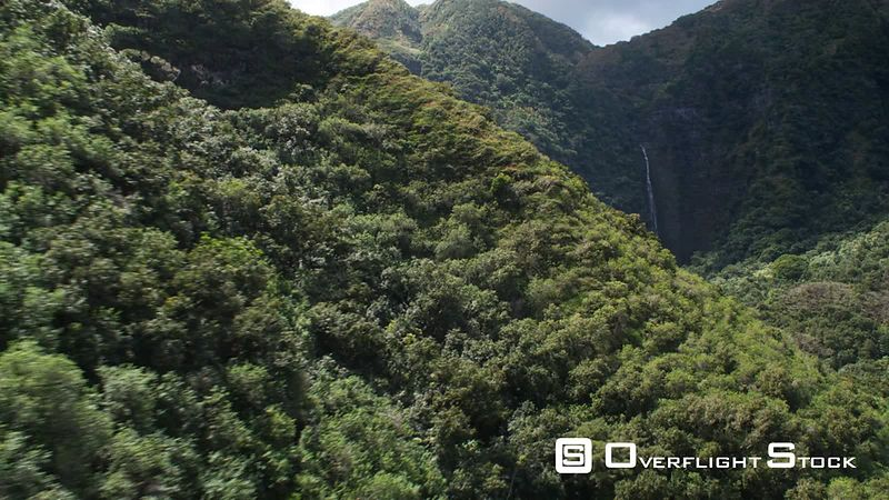 Around a tree-covered hillside to a close view of waterfalls, Molokai.