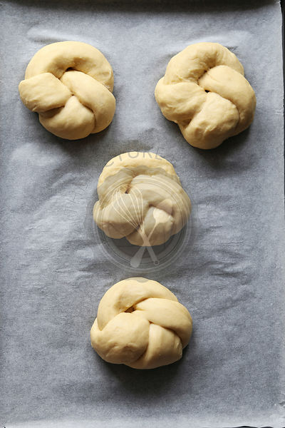 Braided round challah dough on a tray before baking.Top view