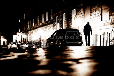 An atmospheric image of a mystery man looking shifty, by a car, in an empty cobbled street, at night.