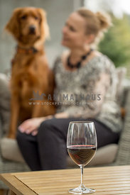 Blonde woman sitting with Irish Setter mix on outdoor chair with wine glass on table