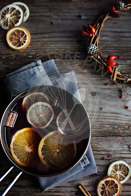 Hot winter drink. Mulled wine with orange, lemon and spices in a casserole on wooden rustic table. Christmas atmosphere