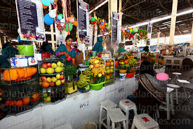 Girl preparing fresh fruit juice on stall in San Pedro market, Cusco, Peru