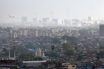An airplane approaches the Mumbai airport, as seen from a 20-story apartment rooftop in the Powai area of Mumbai, India.