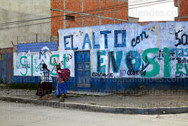 Aymara women walking past slogans on wall showing support for Evo Morales, El Alto, Bolivia