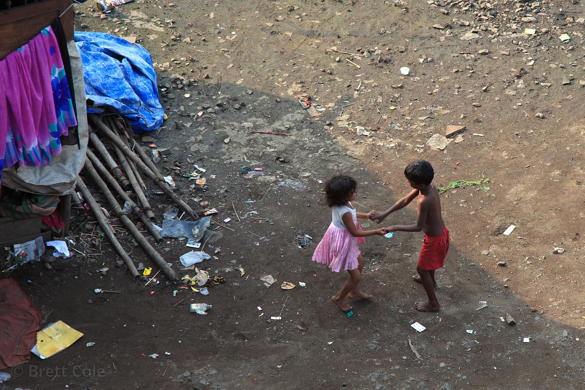 Two children dance in a circle while holding hands, in a slum area in Antop Hill, Mumbai, India.