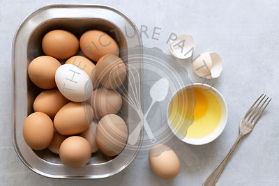 Eggs in a dish with a cracked egg in a bowl.