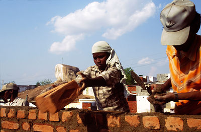 Child labourer builds a wall in a Hyderabad slum