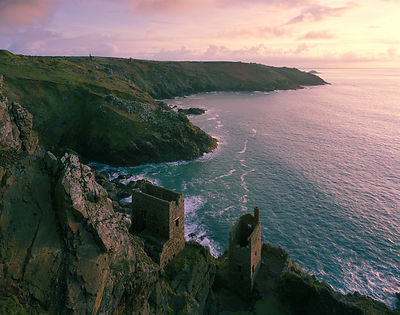 Clifftop view of the ruined mines mines at Botallack as the sun prepares to set.