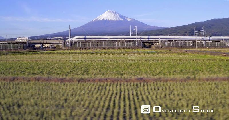 Panning shot of a Shinkansen bullet train passing through harvested rice fields, with Mount Fuji in the background, Honshu, J...