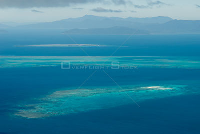 Aerial view of a Sand Cay on the Great Barrier Reef, with Australia's coastline (Cairns area) in the background. Queensland, ...
