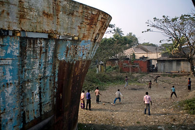 Bangladesh - Chittagong - Boys play cricket in the shadow of a rusty hull of a ship in the docks at Sadarghat