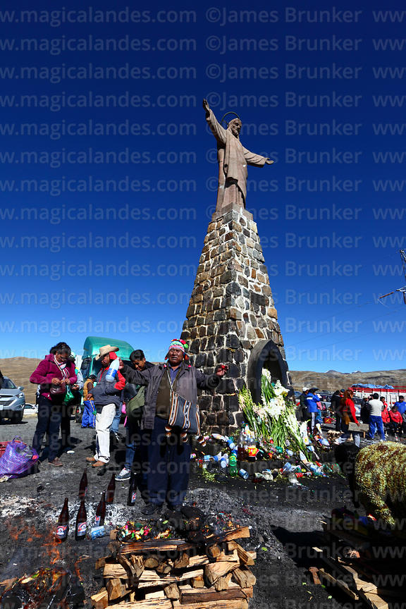 Aymara shaman or yatiri blessing offerings (called a k'oa) to Pachamama below Christ statue, La Cumbre, Cordillera Real, Bolivia