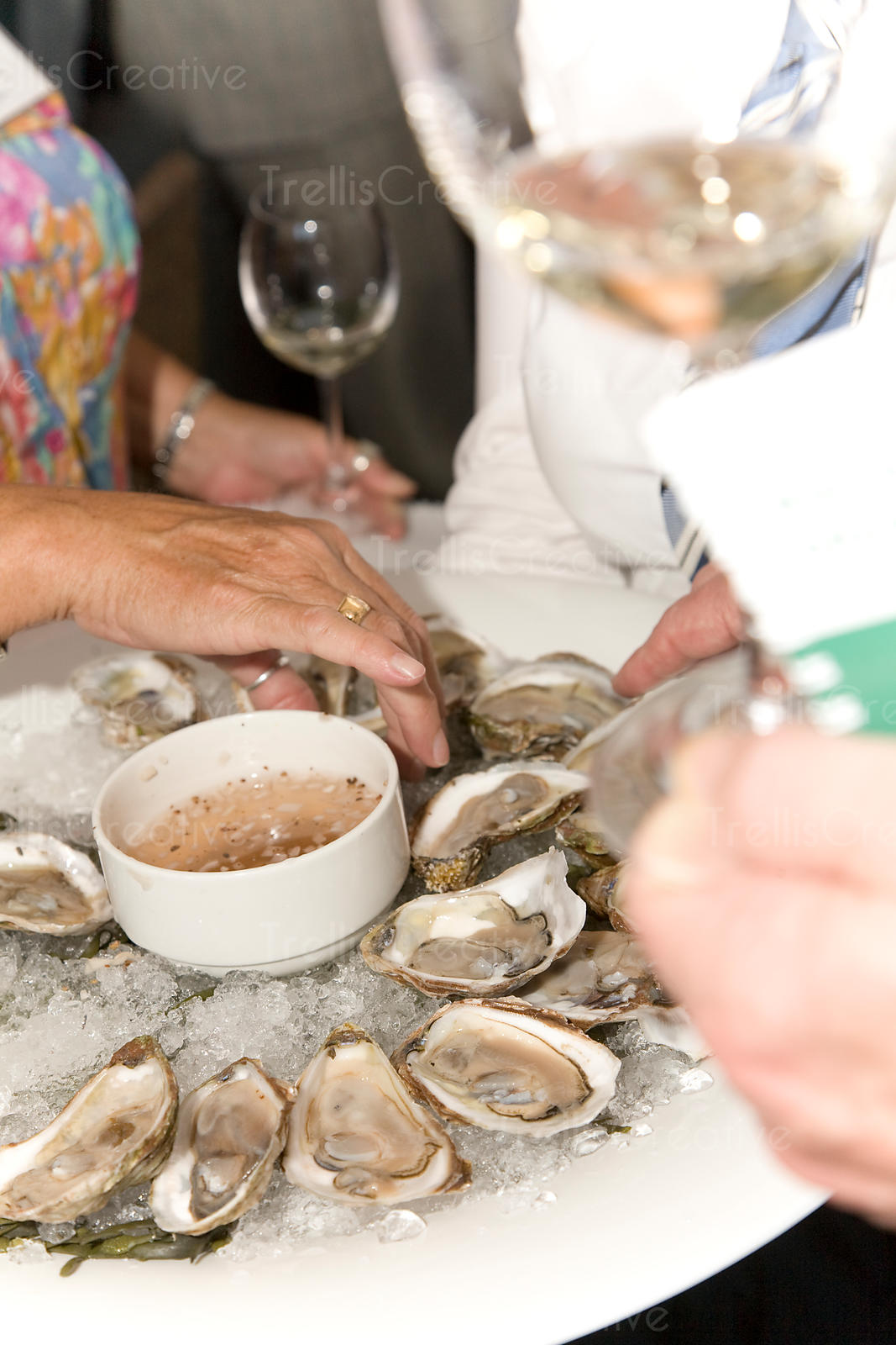 Guests enjoy eating a platter of oysters