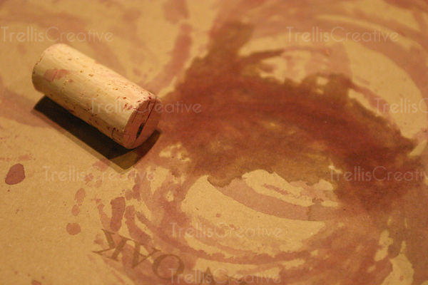 A cork and wine bottle stains on a brown table