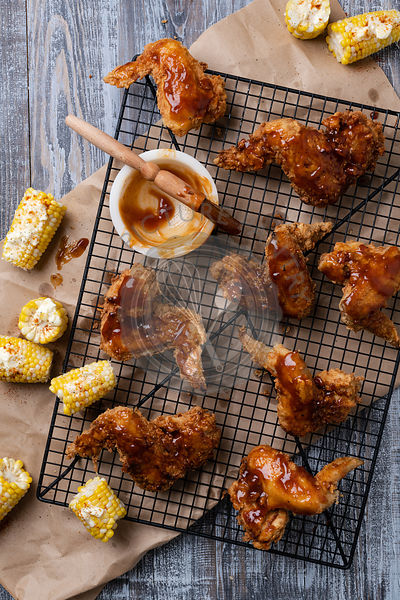 Fried Chicken wings with BBQ sauce and corn.