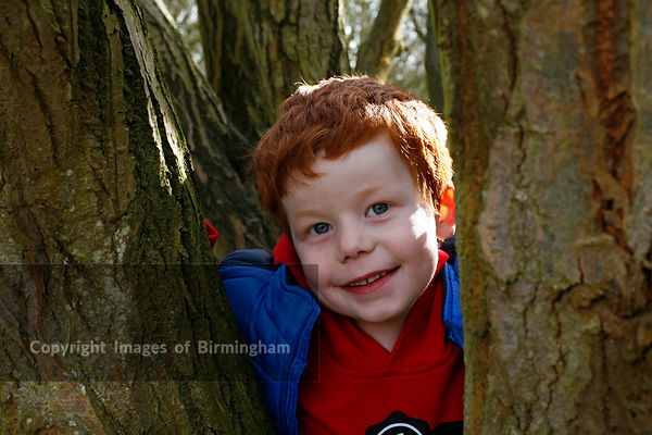 A 7 year old boy playing in the woods.