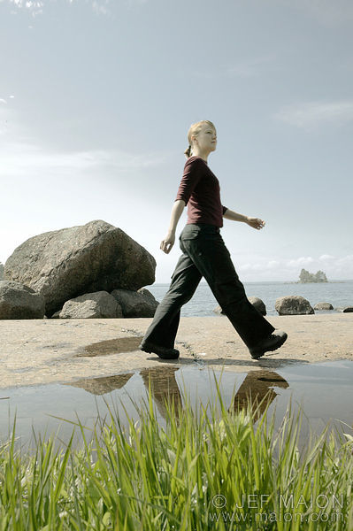 Woman walking on rocky sea shore