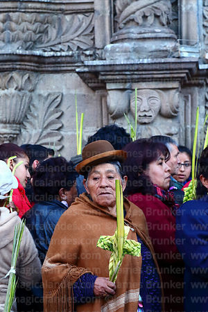 Woman holding cross made out of palm leaves outside San Francisco church before mass on Palm Sunday, La Paz, Bolivia