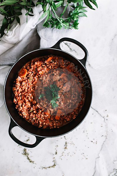A bolognese sauce in a pan on a marble background