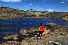 Hiker looking at view across Laguna Patalarama, Cordillera Real, Bolivia