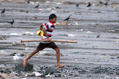 A fisherman runs along Chowpatty Beach in Mumbia, India.