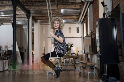 Smiling woman on swing in modern office