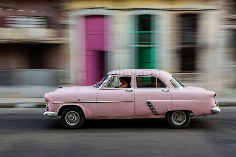 Vintage Amercan Car Driving Past Colorful Doors in Central Havana
