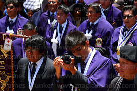 Devotee of Señor de los Milagros filming the central mass for the Virgen de la Candelaria festival using a Canon Rebel T5i di...
