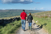 Couple holding hands walking along Roman road heading towards Bainbridge from Burtersett in the Yorkshire Dales National park...