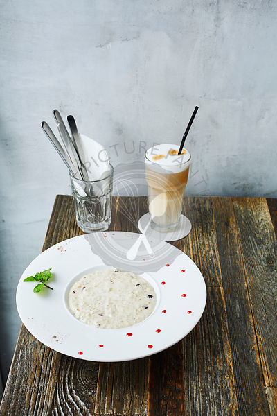 Oatmeal in a white plate with coffee on wooden table at Cafe