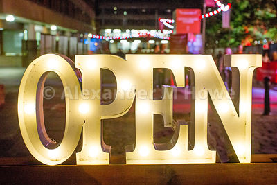 Illuminated OPEN sign against a background of night-time  out of focus lights