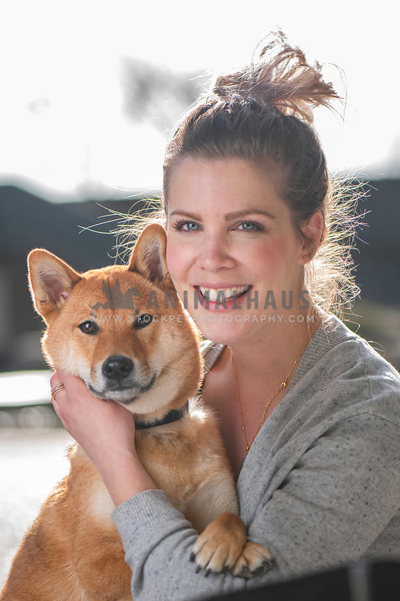 young caucasian dog mom holding shiba inu in her lap
