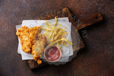 Fish and Chips british fast food with ketchup sauce on dark background