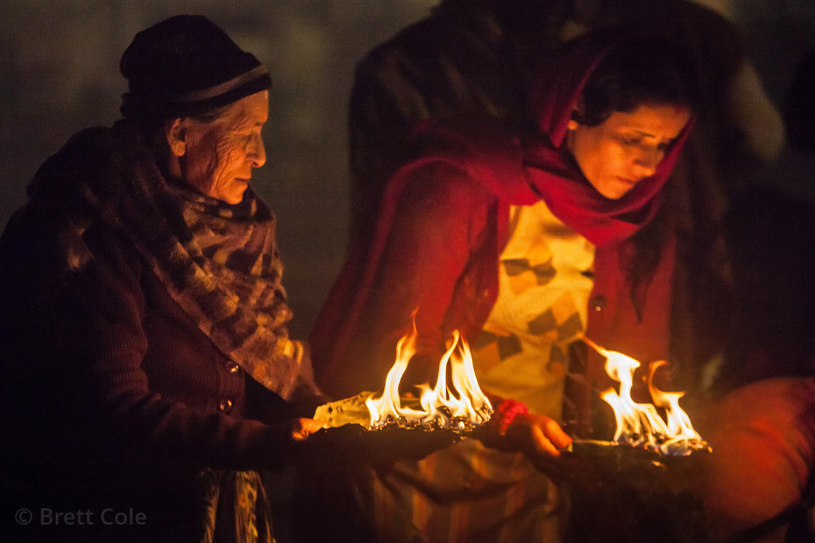 A group of women pilgrims pray on the beach at Sagar Island in the Bay of Bengal during the Gangasagar Mela, India.