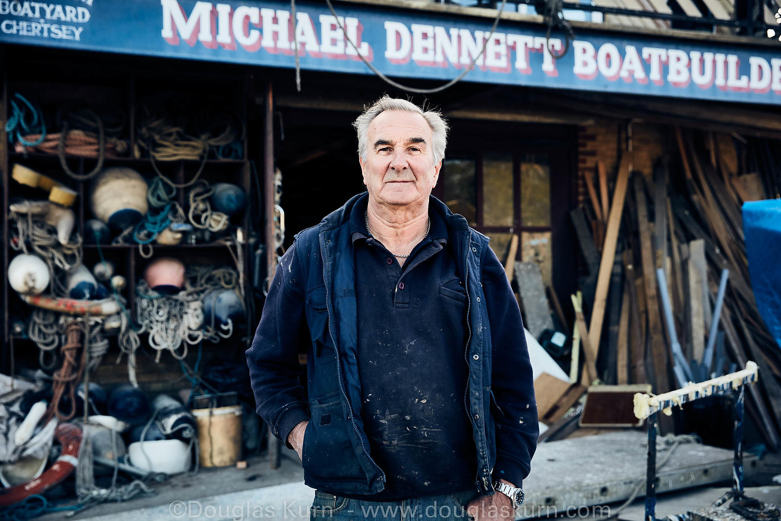 Michael Dennet outside the boathouse of Michael Dennet Boatbuilders