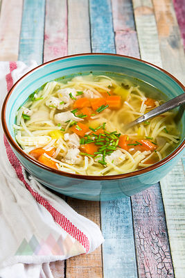 Soup bowl of chicken stock with noodles, carrots and chive