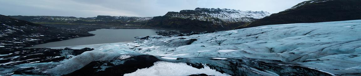 Panoramic photo of the Solheimajokull glacier of blue ice and volcanic sand.