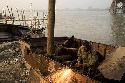 Bangladesh - Chittagong - A man dismantles a boat with a blow torch and hammer on the banks of the Karnaphuli River beneath t...