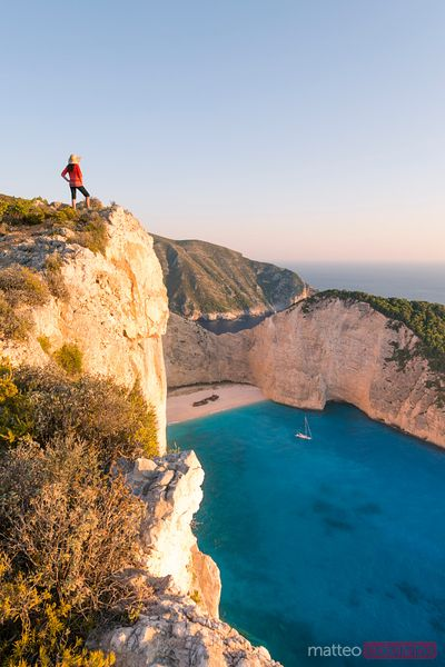 Woman on cliff edge over shipwreck beach. Zakynthos,  Greece