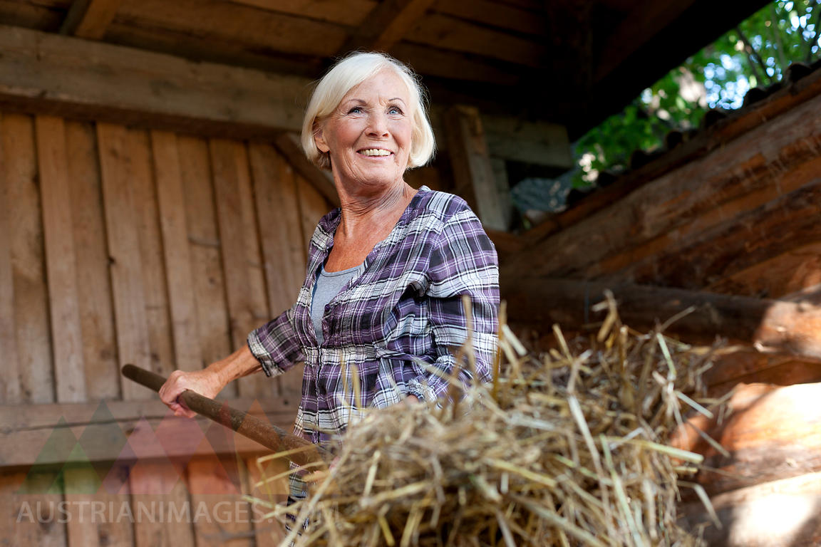 Germany, Saxony, Senior woman working at the farm, smiling