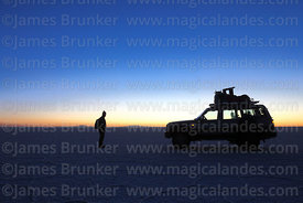 Tourist and Toyota Land Cruiser silhouetted against pre-dawn twilight, Salar de Uyuni , Bolivia